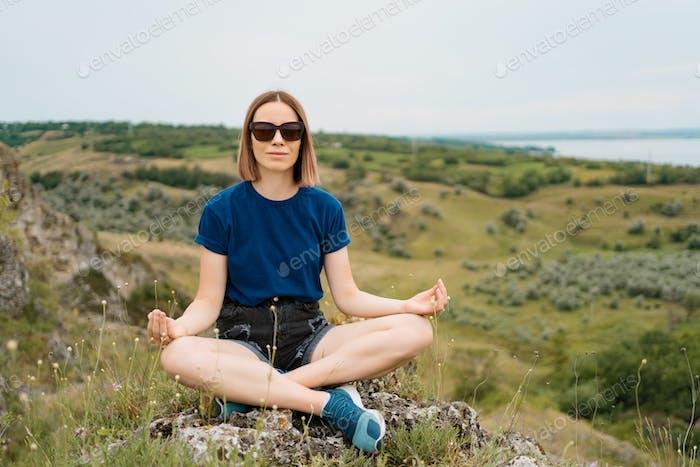 Yoga Frau meditieren auf Hügel Gipfel Klippe Rand
