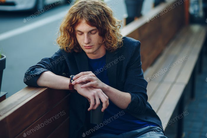 Man looking to the watch on his hand