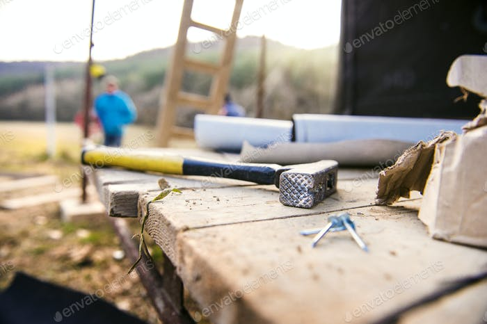 Hammer, nails on wooden boards outside on construction site