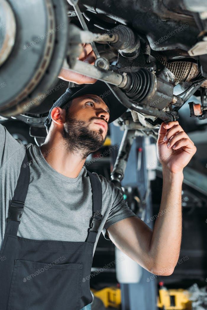 professional engineer in overalls repairing car in mechanic shop