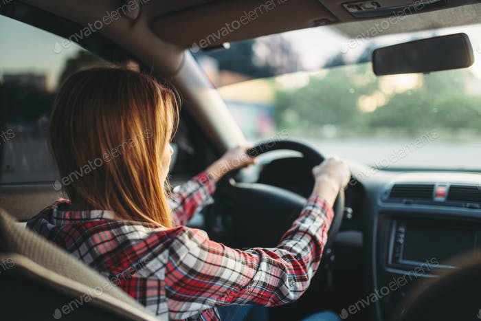 Young woman beginner driving a car, back view