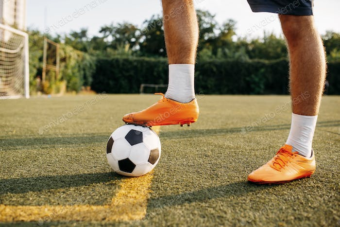 Male soccer player legs with ball standing on line