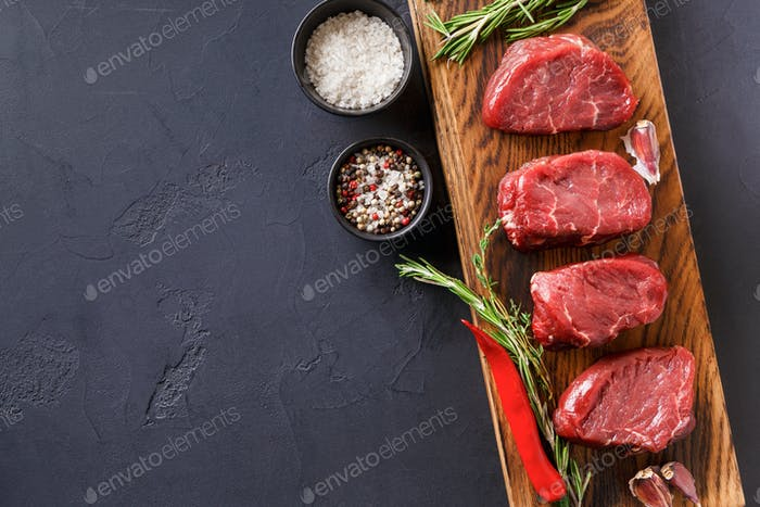 Filet mignon steaks and spices on wood at black background