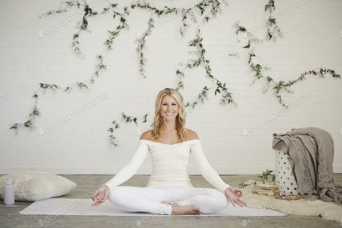 A blonde woman seated in a yoga pose
