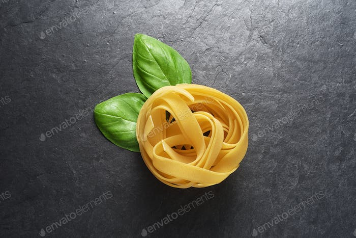 Fettuccine pasta with basil leaves on black background