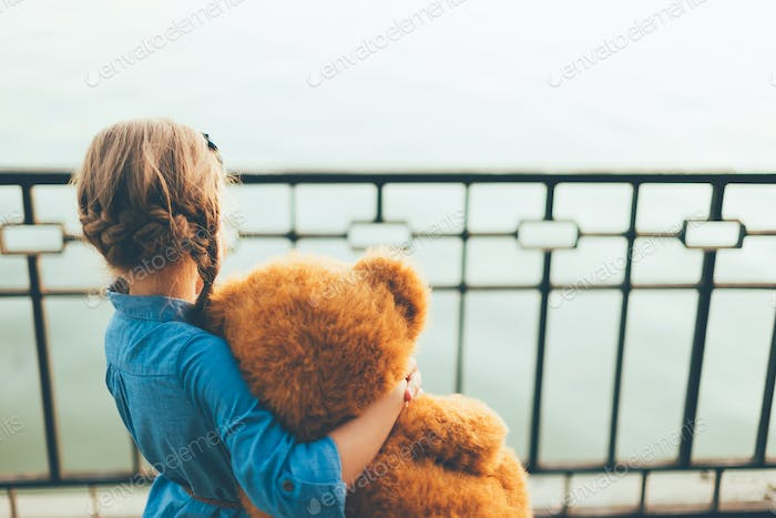 Back view of girl embracing a cute teddy bear looking to lake