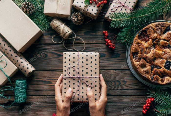 Female hands hold one gift in polka dot wrapping paper. Cute Christmas flat lay. Festive concept.