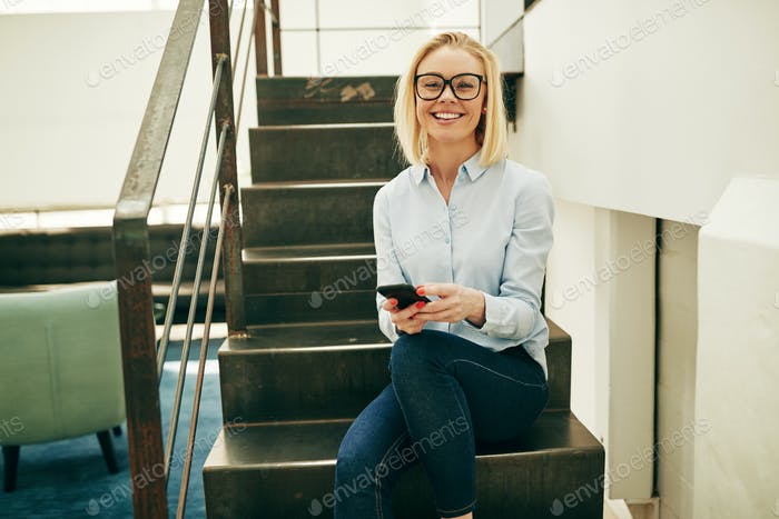Smiling businesswoman sitting on office stairs sending text messages