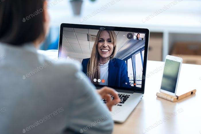 Weibliche Mitarbeiterin spricht auf Video anruf mit ihrer Kollegin auf Online-Briefing mit Laptop zu Hause.
