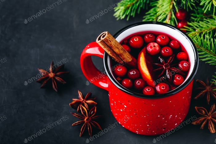 Traditional Christmas Mulled Wine drink with cranberries, orange slices and spices in red mug
