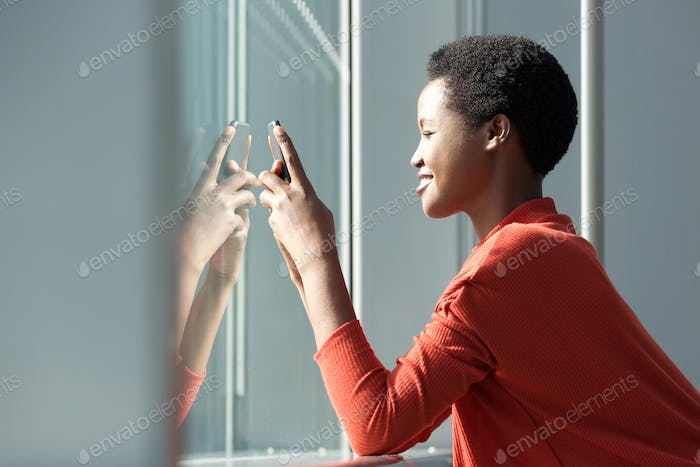 Profile of beautiful smiling african american woman looking at mobile phone by window