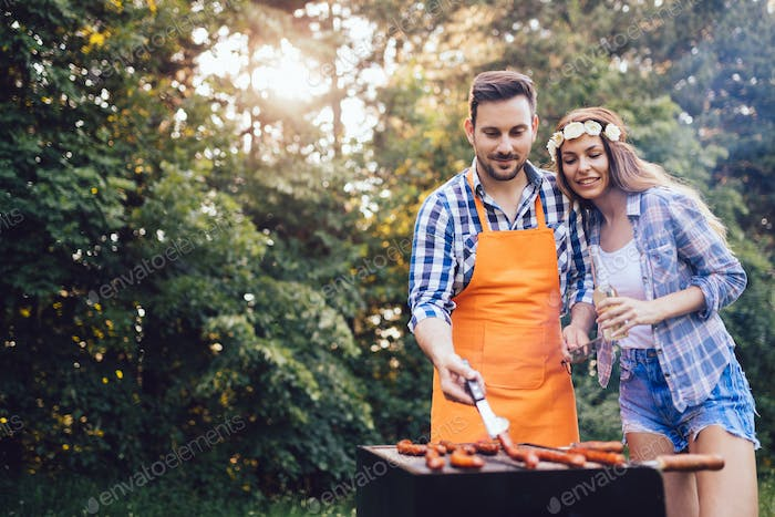Beautiful woman and handsome man having barbecue
