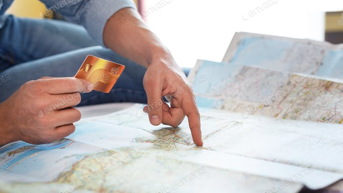 Man holding credit card on world map background