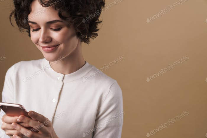 Image of cheerful seductive woman using cellphone and smiling