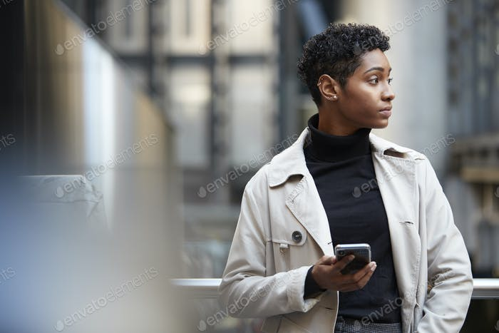 Young black businesswoman standing in the city with smartphone in hand, close up, selective focus