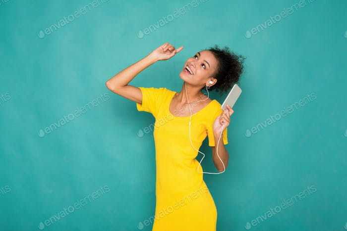 Woman listen to music in earphones, studio shot