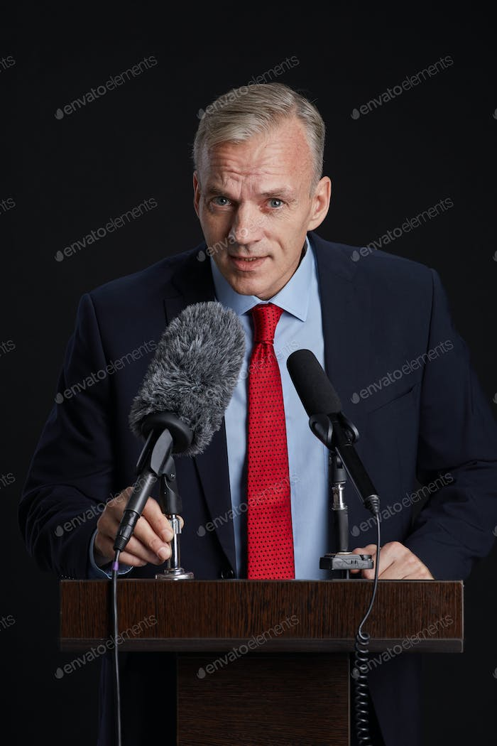 Mature Man Speaking to Microphone at Podium