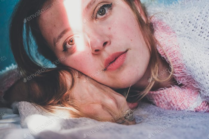 Portrait of a young woman with her face crossed by a sun shine