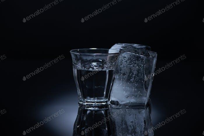 Transparentes Glas mit Eiswürfel und Wodka auf schwarzem Hintergrund