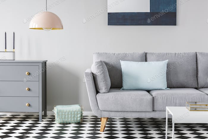 Pink lamp above grey cabinet next to sofa on checkered floor in