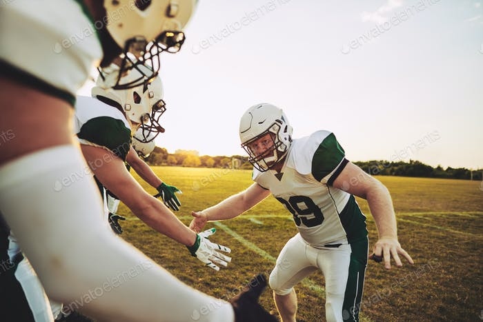 American football player giving his teammates low fives after practice