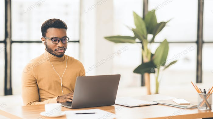 Concentrated afro guy in eyewear typing on keyboard