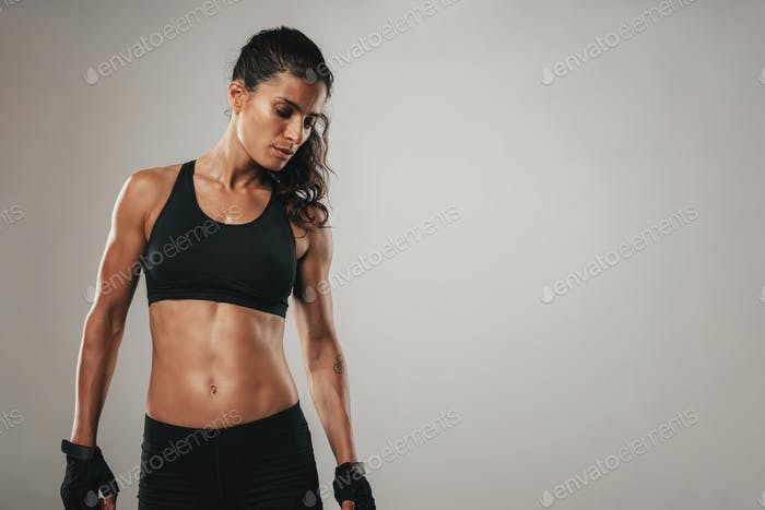 Strong woman in black athletic garments stands