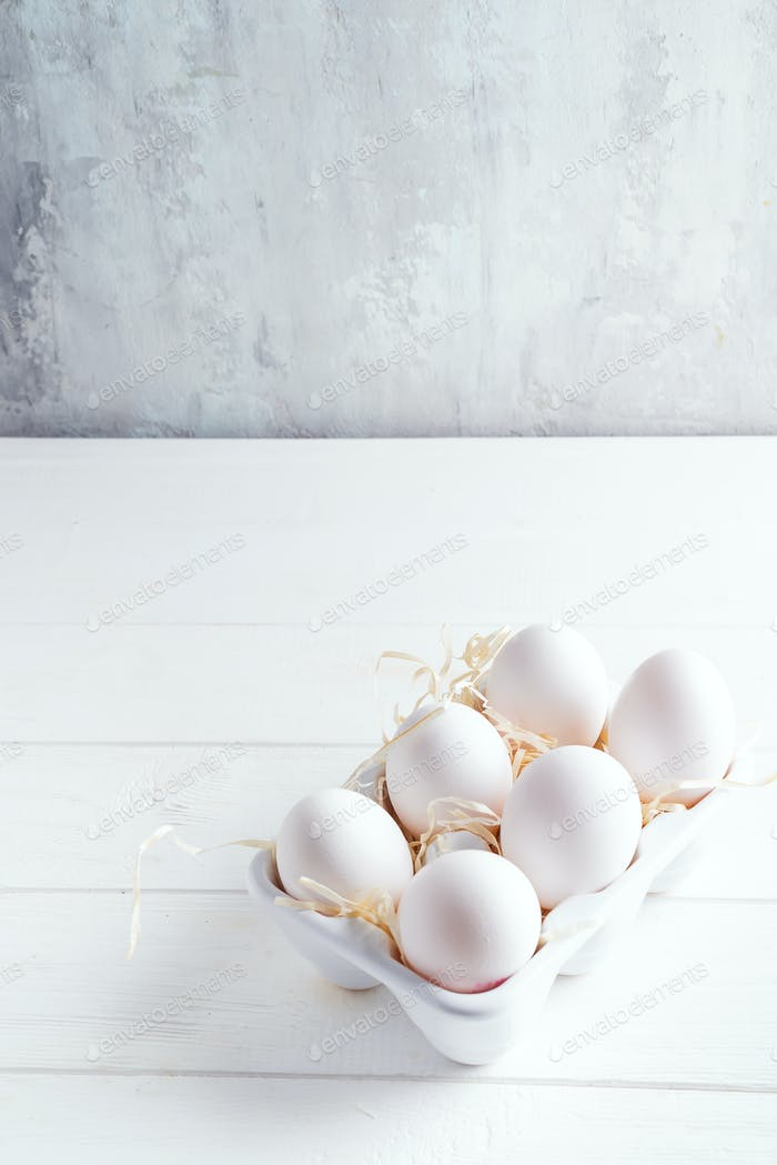 Organic white chicken eggs in porcelain decorative box on white. Natural healthy food and organic