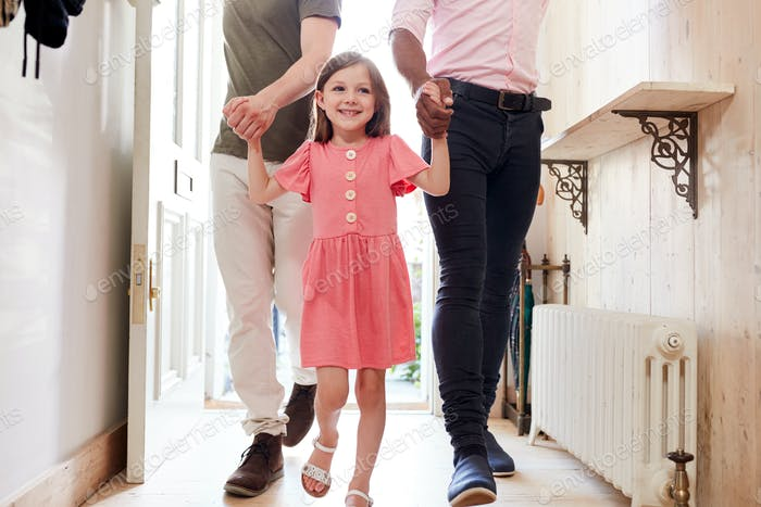 View Inside Hallway As Same Sex Male Couple With Daughter Open Front Door Of Home