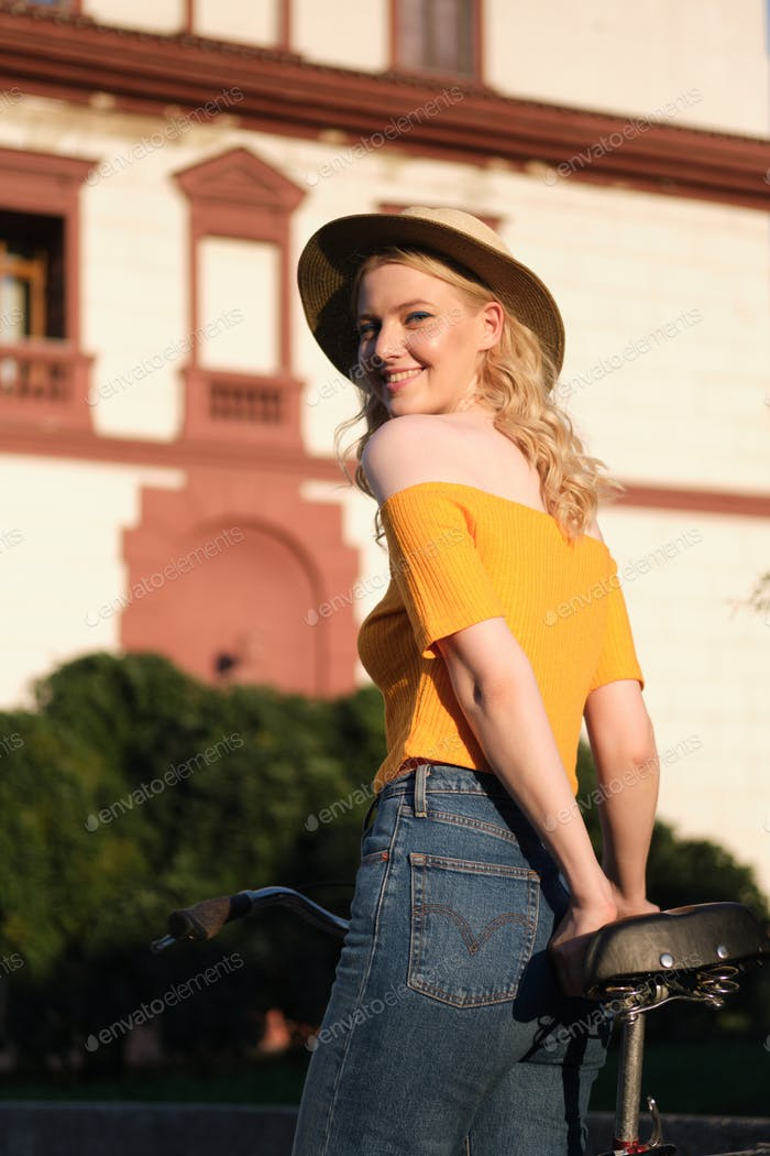 Attractive cheerful blond girl in hat standing with bicycle happily looking in camera on city street