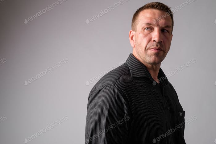 Portrait of macho mature businessman thinking and looking back