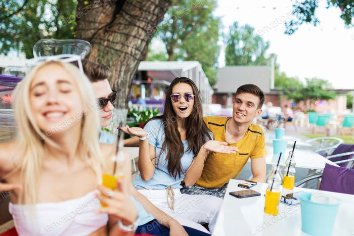 A company of good-looking friends laughing and drinking yellow cocktails and socialising at the