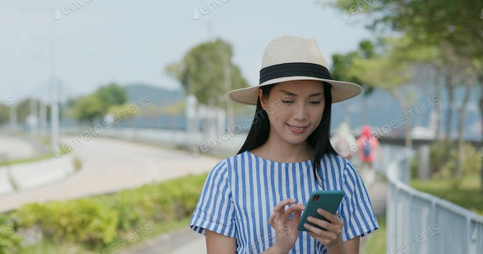 Woman search on cellphone of the location in city
