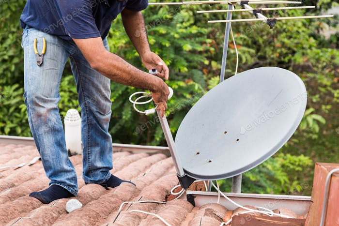 Worker installing satellite dish and antenna on roof top