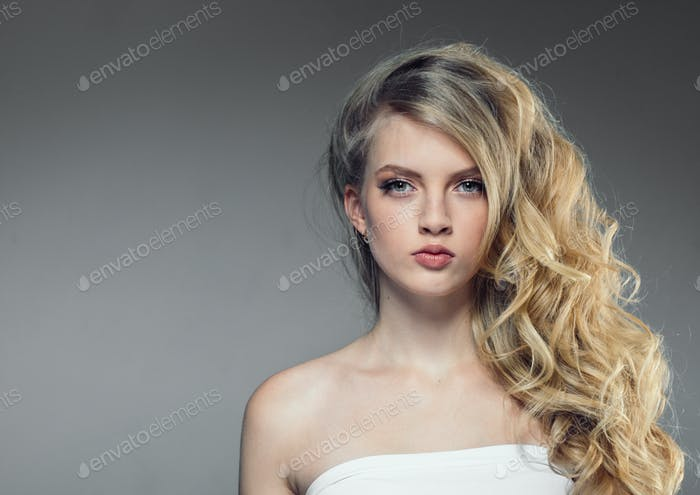 Beautiful woman portrait with fresh daily make-up blonde curly hair and healthy skin