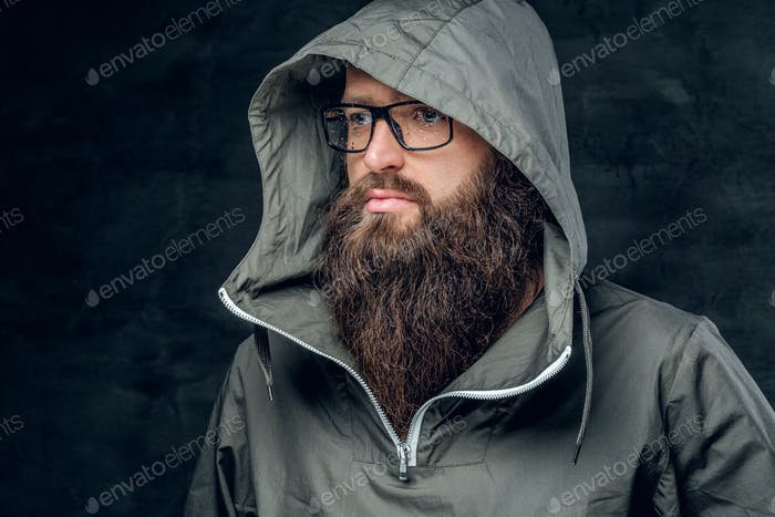 Bearded male in a hood on grey background.