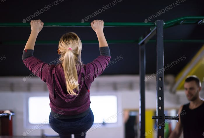 woman doing pull ups on the horizontal bar