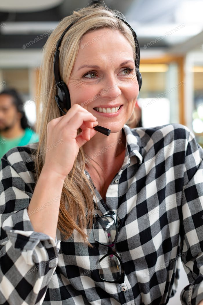 Happy Caucasian female customer service executive looking away while talking on headset