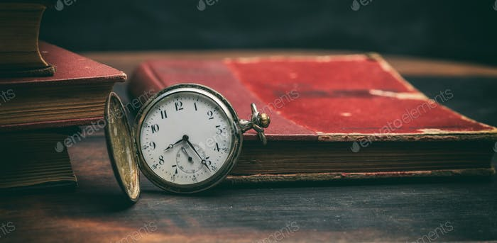 Vintage books and pocket watch on dark background