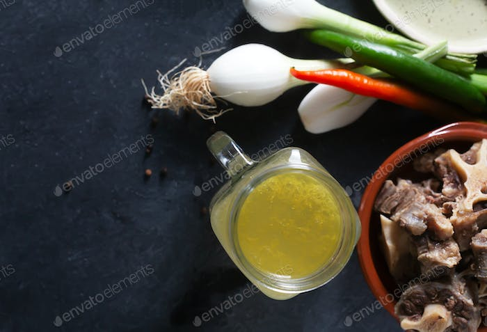 Homemade Beef Bone Broth in Glass Storage Jar on a black background, top view