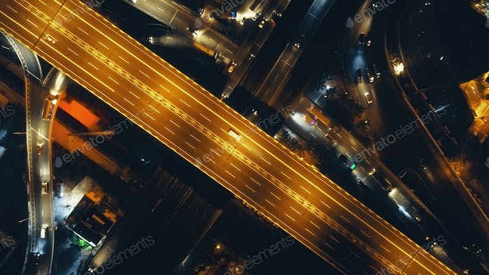 Top down night illuminate traffic highway aerial. Metropolis cityscape with modert neon road