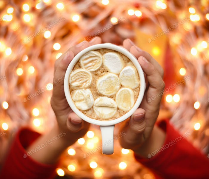 Children's hands hold a cup of cocoa with marshmallows. Autumn o