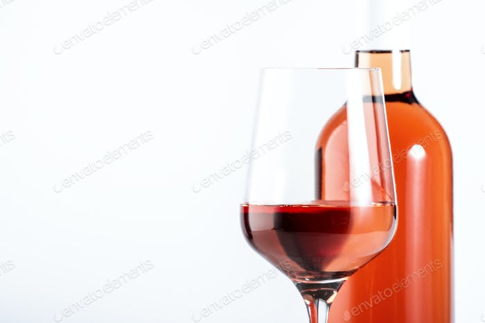 Rose wine glass with bottle on the white table. Rosado, rosato or blush wine tasting
