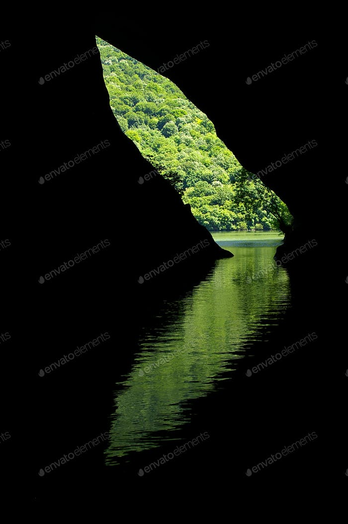 Reflection of a mystic cave entrance in the water