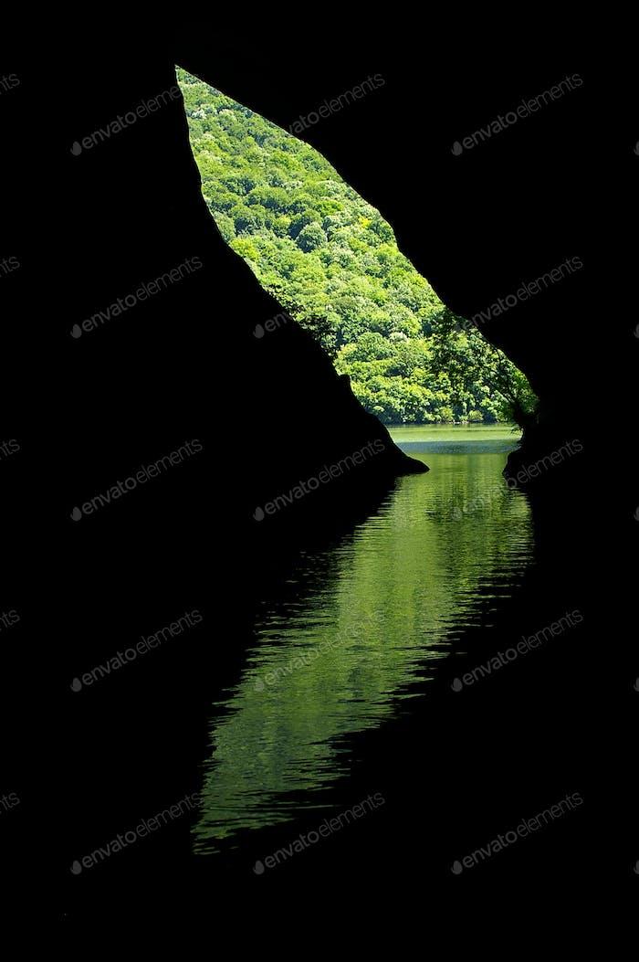 Reflexion eines mystischen Höhleneingangs im Wasser