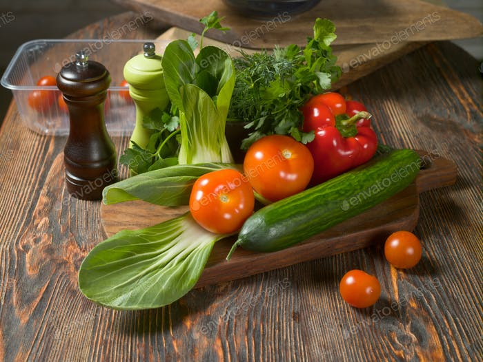 Fresh vegetables and fresh herbs lie on a wooden table