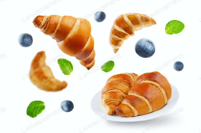 Flying croissants with blueberries and mint leaves isolated