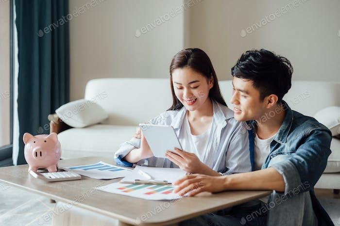 Junges Paar, das zu Hause zusammen arbeitet