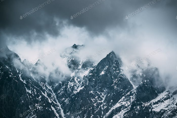 Clouds Fly Low Over Rocks. Mountains Peaks Covered With Snow. Va