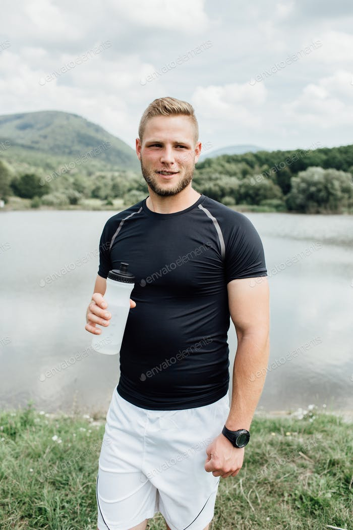 Smiling male runner standing at a pond with a bottle of water